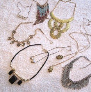 Clockwise from top left: White Feather Designs' geometric silver and gold,  Kensington Market graphic beads, E-bay $10 gold collar, 2 long pendants from YYZ Imports, H&M silver fringe, black and gold statement piece from a garage sale, Joe Fresh $5 sale baubles/rinestone necklace