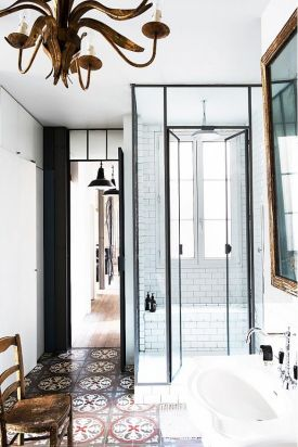 A bohemian Parisian flat boasts tall narrow spaces, but doesn't skimp on style. The classic black and white, with glass and antiques creates a balance in contrasts. Found on domainehome.com