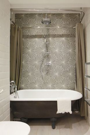 I grew up in a century home, in tiny Waterdown, Ontario, in a colonial center hall stone house. Our tiny second floor bathroom had a claw-foot tub. The beautiful tub, pictured here, perfectly balances old with new and the splash of graphic wallpaper makes it quite modern. Photo: Industrial Bathroom by Oliver Burns