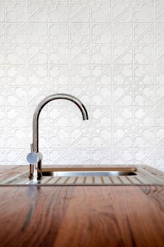 A sleek curved faucet is modern and clean against the backdrop of painted tin. What a beautiful way to add texture to a kitchen. I've always wanted a gilded tin ceiling, or one with peeling, distressed paint.