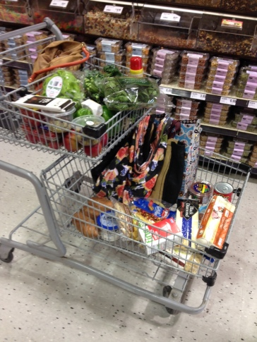 A moderately full cart. Mostly greens and whole grains. Lots of re-usable shopping bags.