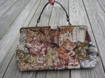 My purse (not the one in the photo) is a medium brown, much more substantial piece with studs on the flat bottom and a shoulder/cross body strap. However, the embroidery is pretty much in line with the image above.